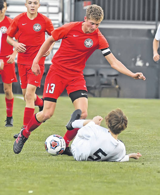 Bluffton's Simon Derstine dribbles past Wellington's William Starker during Sunday's Division III State Championship match at Mapfre Stadium in Columbus.