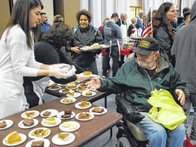 Ted Downey, of Lima, made sure to pick up some pie for dessert Thursday before leaving the free Thanksgiving dinner held at the Civic Center.