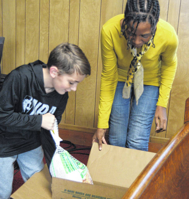 Jacob Carge and Karen Capers help pack Thanksgiving boxes Sunday in an effort to help 10 sixth ward Lima families.