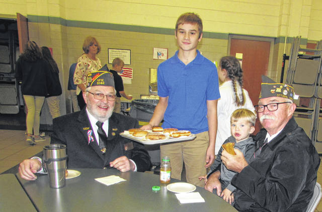 Nick Ellerbrock, SS. Peter & Paul eighth grader, serves breakfast to Ken Wehri, left, Ottawa VFW Post 9142 member and his grandson Butch Askins and Dave Yoder, Ottawa VFW member.