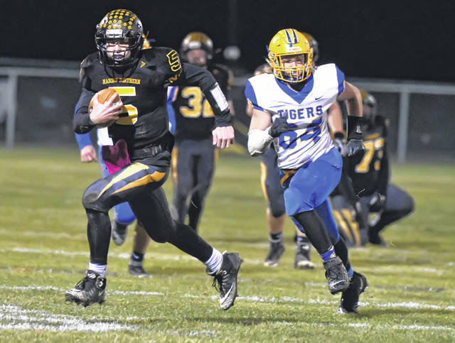 Waynesfield-Goshen's Jakob Augsburger pursues Hardin Northern's Nevin Robson during Friday night's game in Dola.