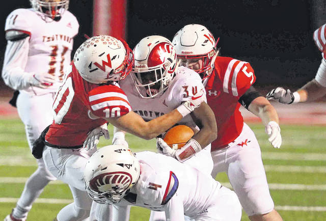 Wapakoneta's Braeden Goulet, left, and Evan Kaeck combine to tackle Trotwood-Madison's Hezekiah Hudson-Davis during Friday night's Division VI quarterfinal in Wapakoneta.