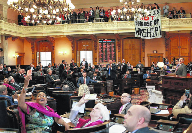 "FILE - In this April 10, 2019 file photo, some members of the Ohio House applaud following their vote while others photograph protestors who unfurled banners reading ""This is not a House of Worship"" and ""This is not a Doctor's office"" following a vote on the Heartbeat Bill at the Ohio Statehouse in Columbus, Ohio. A group of conservative lawmakers in Ohio has introduced a bill to outlaw abortion outright, declaring a fetus a person and subjecting doctors who terminate pregnancies to potential murder charges. The legislation introduced Thursday, Nov. 14, appears to make an exception for the life of the mother."