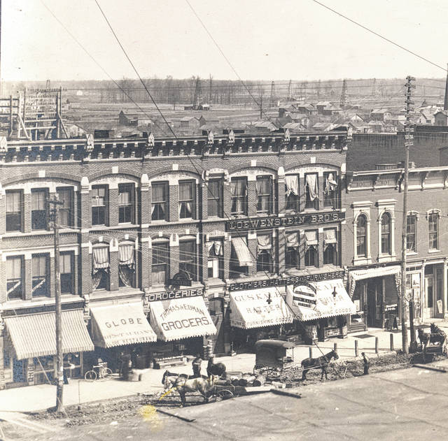 This photo of downtown Lima after 1895 shows the store then called Loewenstein Brothers across the facade and Gus Kalb hatter and clothier on the awnings. A smaller sign states Loewenstein Brothers are successor to Gus Kalb. Note the oil derricks in the background, then rather open land with few houses.