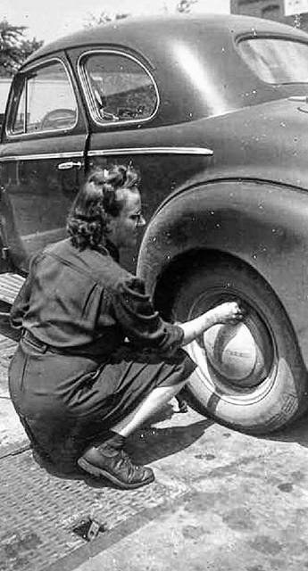 An unidentified worker checks the air in a customer's tire.