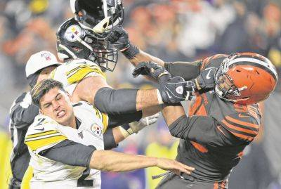 The Browns' Myles Garrett hits Pittsburgh's Mason Rudolph (2) with a helmet during Thursday night's game in Cleveland.