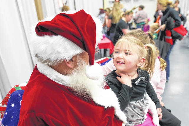 Three-year-old Isabelle Clementz, of Lima, reacts to Santa during the Activate Allen County Healthy Families Expo held at Veterans Memorial Civic Center Saturday morning.