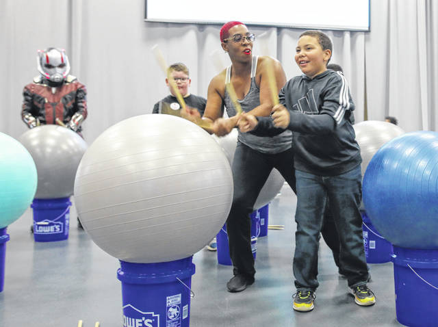 Tesha Banks, program coordinator of the Brafield Center, teaches Pound techniques to 8-year-old Caiden Luke (right) of Lima during the Activate Allen County Healthy Families Expo held at Veterans Memorial Civic Center Saturday morning.
