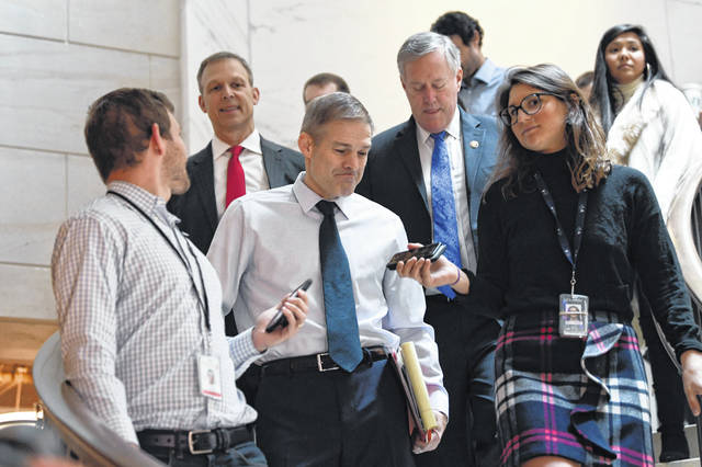 Rep. Jim Jordan, R-Ohio, center, Rep. Scott Perry, R-Pa., second from left, and Rep. Mark Meadows, R-N.C., fourth from left, are surrounded by reporters on Capitol Hill in Washington, Thursday, Nov. 7, 2019, as they head to a closed-door interview in the impeachment inquiry on President Donald Trump's efforts to press Ukraine to investigate his political rival, Joe Biden.