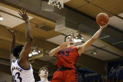 Dayton's Ryan Mikesell, a St. Henry graduate, puts up a shot against Kansas' David McCormack during Wednesday's  Maui Invitational title game in Lahaina, Hawaii. (AP photo)