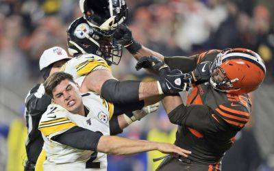 The Browns' Myles Garrett (95) hits Pittsburgh's Mason Rudolph (2) with a helmet during Thursday night's game in Cleveland. (AP photo)