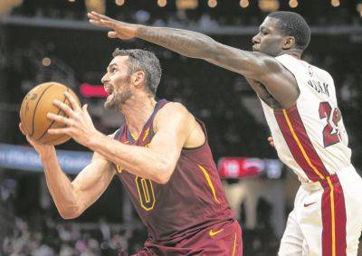 The Cavaliers' Kevin Love drives past Miami's Kendrick Nunn during Thursday night's game in Cleveland.