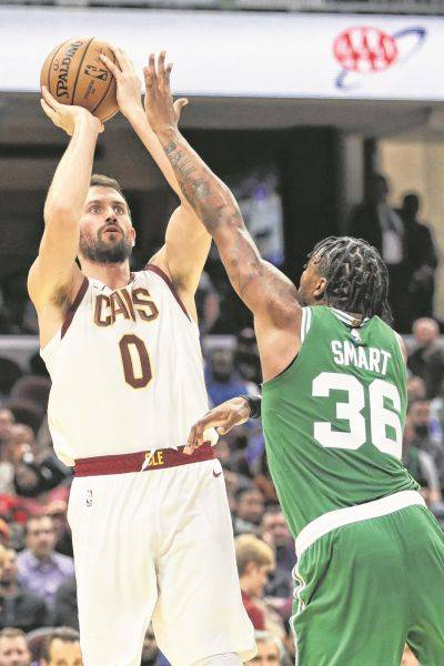 The Cavaliers' Kevin Love (0) puts up a shot against Boston's Marcus Smart during Tuesday night's game in Cleveland.
