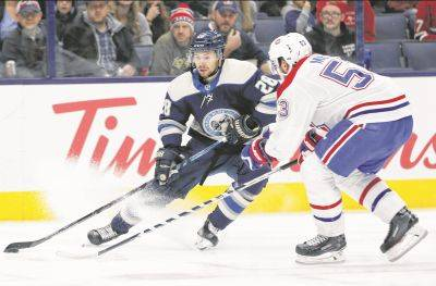 The Blue Jackets' Oliver Bjorkstrand, left, looks to pass as Montreal's Victor Mete defends during Tuesday night's game in Columbus.