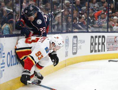 Calgary's Sam Bennett, bottom, checks the Blue Jackets' Sonny Milano during Saturday night's game in Columbus. (AP photo)