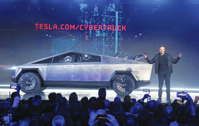 "FILE - In this Nov. 21, 2019 file photo, Tesla CEO Elon Musk introduces the Cybertruck at Tesla's design studio in Hawthorne, Calif. The much-hyped unveil of Tesla's electric pickup truck went off script Thursday night when supposedly unbreakable window glass shattered twice when hit with a large metal ball. The failed stunt, which ranks high on the list of embarrassing auto industry rollouts, came just after Musk bragged about the strength of ""Tesla Armor Glass"" on the wedge-shaped ""Cybertruck."""