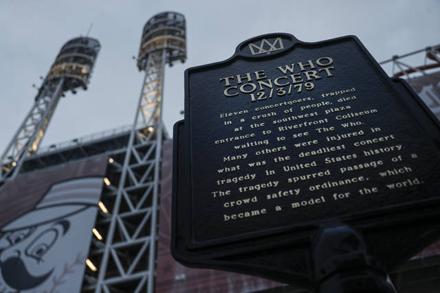 In this Wednesday, Nov. 20, 2019 photo, a memorial plaque for eleven concertgoers killed at a 1979 concert stands between Great American Ballpark and Heritage Bank Arena,  in Cincinnati. Tragedy four decades ago linked the British rock band The Who to a small suburban city in Ohio. In recent years, members of the community and the band have bonded through a project to memorialize the three teens from Finneytown who were killed in a frantic stampede of people trying to get into The Who's Dec. 3, 1979, Cincinnati concert. (AP Photo/John Minchillo)
