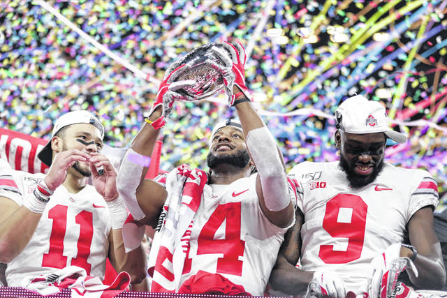 Ohio State wide receiver K.J. Hill (14) holds the trophy following the team's 34=21 win over Wisconsin in the Big Ten championship NCAA college football game, early Sunday, Dec. 8, 2019, in Indianapolis. (AP Photo/Michael Conroy)