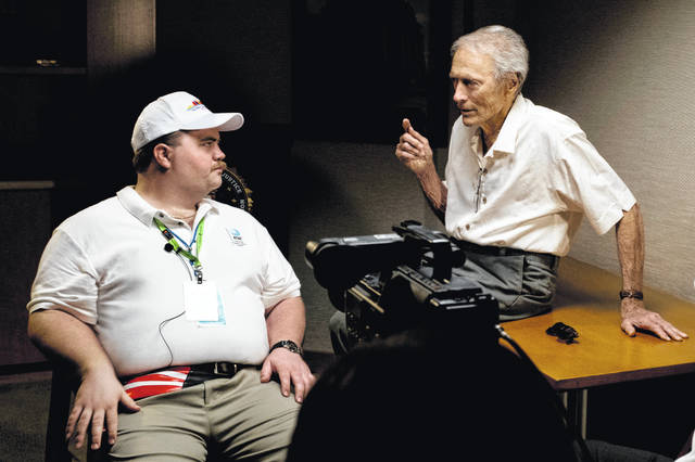 """In this image released by Warner Bros. Pictures, director Clint Eastwood speaks with actor Paul Walter Hauser as they work during the filming of the movie """"Richard Jewell."""""""