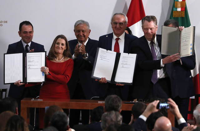 Mexico's Treasury Secretary Arturo Herrera, left, Deputy Prime Minister of Canada Chrystia Freeland, second left, Mexico's President Andres Manuel Lopez Obrador, center, Mexico's top trade negotiator Jesus Seade, second right, and U.S. Trade Representative Robert Lighthizer hold the documents after signing an update to the North American Free Trade Agreement at the national palace in Mexico City on Tuesday.