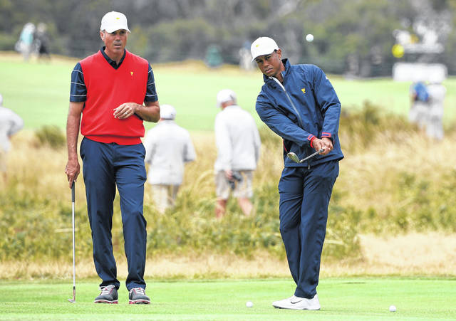 USA's Matt Kuchar, left and team captain Tiger Woods during a practice round ahead of the President's Cup golf tournament in Melbourne, Australia, Wednesday, Dec. 11, 2019. (AP Photo/Andy Brownbill)