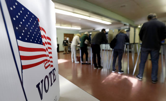 FILE - In this Nov. 6, 2018, file photo, voters cast their ballots, in Gates Mills, Ohio. An Associated Press review has found that thousands of Ohio voters were held up or stymied in their efforts to get absentee ballots by mail in 2018's general election because of a missing or mismatched signature on their ballot application. (AP Photo/Tony Dejak, File)