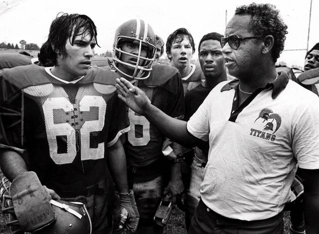 """This 1971 file photo shows Alexandria, Va's., T.C. Williams High School football coach Herman Boone, right, during a break at summer camp, with guard Johnny Colantuoni (62) and John Vaughn, center. Boone, the Virginia high school football coach who inspired the movie """"Remember the Titans,"""" has died. He was 84."""
