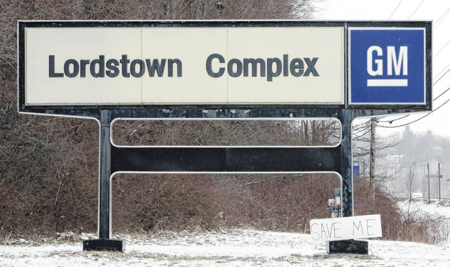 "A ""Save Me"" sign rests against the Lordstown Complex sign on March 6 in Lordstown. Youngstown faces competition in its efforts to become a research and production hub with places such as Detroit and China that are taking big roles in developing electric vehicles."