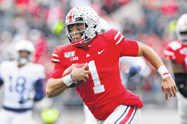 FILE - In this Nov. 23, 2019, file photo, Ohio State quarterback Justin Fields plays against Penn State during an NCAA college football game, in Columbus, Ohio. Fields, a sophomore and the Buckeyes' Heisman Trophy finalist quarterback, said online classes allow him to split his time between studying at home or relaxing with Netflix and the Woody Hayes Athletic Center, where besides football facilities there is a new lavish lounge for players that offers made-to-order meals, massage chairs, video games on big screens and a cryogenic chamber. (AP Photo/Jay LaPrete, File)