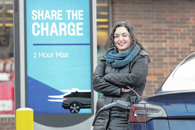 "Neda Deylami charges her electric vehicle Dec. 20 at a Chicago area grocery store. Owners of electric vehicles in a number of states will start seeing fees to pay for road repairs in the new year. At least eight states will begin charging new or higher registration fees for electric vehicles or plug-in hybrids. ""It's kind of a blanket penalty for anyone who chooses to go electric,"" said Deylami, a Tesla owner who founded Chicago for EVs, a group that advocates for electric vehicles."
