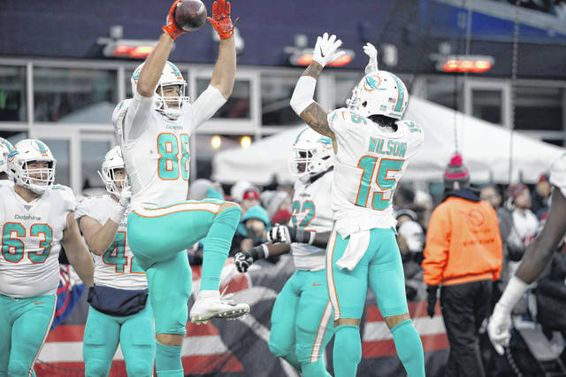 Miami Dolphins tight end Mike Gesicki, left, celebrates his winning touchdown catch with Albert Wilson, right, in the second half of an NFL football game against the New England Patriots, Sunday in Foxborough, Mass.