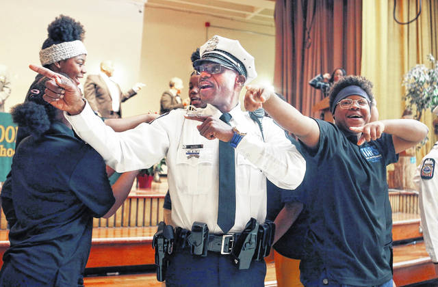 Columbus Police officer George White join students Jahniah Jenkins 13, and Kyrah Green 13, right, in a affirmation of of graduating from the TAPS (Teen and Police Services) program at Sherwood Middle School November 21, 2019.The Columbus Police Department has visited Columbus City Schools to mentor groups of middle school students, with a goal of improving youth-police relations and encouraging children to make good choices. More than two dozen Sherwood Middle School students graduated from the program.