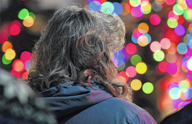 In this Thursday, Dec. 5, 2019, photo a woman watches as a brightly lit float passes by during the Christmas parade Thursday night in downtown Bristol, Va.