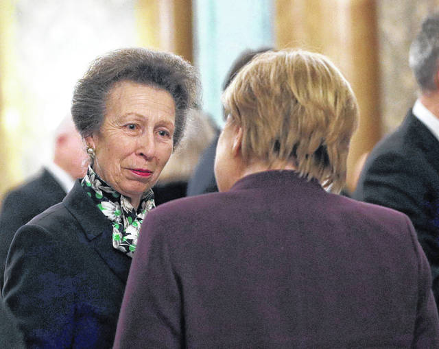 "FILE - In this Dec. 3, 2019 file photo, Britain's Princess Anne, left, talks to the Chancellor of Germany Angela Merkel during a reception at Buckingham Palace, as NATO leaders gather to mark 70 years of the alliance, in London. A shorter video shows Britain's Queen Elizabeth II reprimanding her daughter Princess Anne for not greeting President Donald Trump at a NATO reception at Buckingham Palace. Princess Anne had already escorted President Donald Trump and wife, Melania, to shake hands with the monarch when the queen turned and looked at her daughter. ""It's just me,"" Anne said, motioning that no more world leaders were left in the greeting line. A shorter version of the clip appears to show the queen glaring at her daughter. A longer clip shows that Princess Anne walked in with Trump and the first lady."