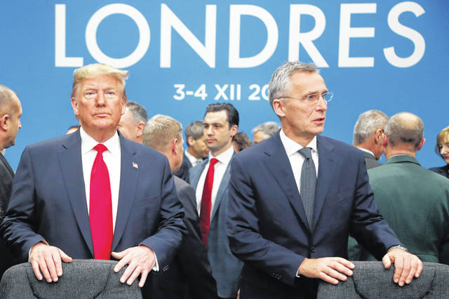 In this Dec. 4, 2019, photo, U.S. President Donald Trump and NATO Secretary General Jens Stoltenberg wait to take their seats prior to a NATO leaders meeting at The Grove hotel and resort in Watford, Hertfordshire, England. Three years into the Trump presidency, America's new place in the world is coming into focus, with influence waning from NATO meeting rooms to the Middle East to the capital cities of key allies. And in many ways, that's just fine with the White House.