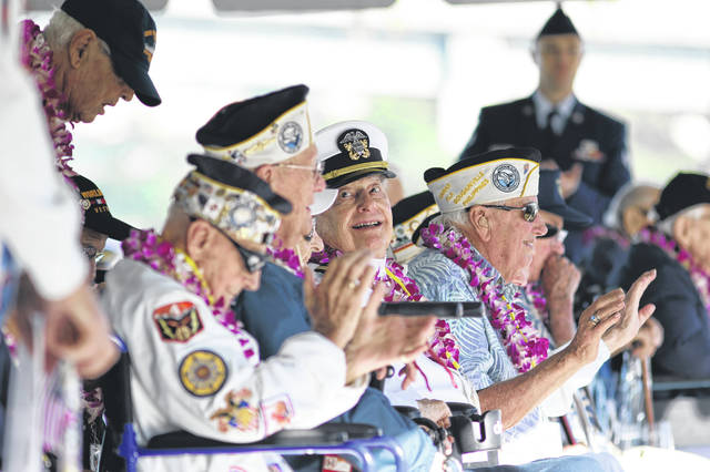 Pearl Harbor survivor Lou Conter, 98, center, who was the only survivor from the USS Arizona to make it to this year's ceremony, smiles during the 78th anniversary of the Japanese attack on Pearl Harbor, Saturday, Dec. 7, 2019 at Pearl Harbor, Hawaii. Survivors and members of the public gathered in Pearl Harbor to remember those killed when Japanese planes bombed the Hawaii naval base 78 years ago and launched the U.S. into World War II. About a dozen survivors of the attack attended the annual ceremony, the youngest of whom are now in their late 90s.