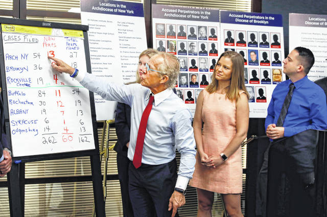 Attorney Jeff Anderson, left, points to a chart of sexual abuse perpetrators during a news conference in New York in August, accompanied by sexual abuse victims Birdie Farrell, center, and Joseph Carramano. When he was a teenager, Caramanno had been hospitalized for an anxiety disorder, and part of his return to high school involved mandated meetings with a priest who controlled his medication. It was during those sessions that he said Monsignor John Paddack fondled him.