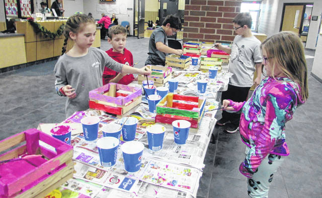 Putnam County YMCA Santa Camp campers work on painting boxes for Christmas presents.