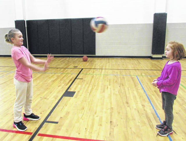 Aubrie Bogart, left, and Izabel Utentorf, Putnam County YMCA Christmas Camp campers, play volleyball in the gym.