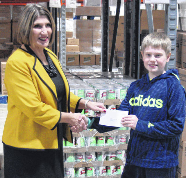 Linda Hamilton with West Ohio Food Bank receives a check from Jacob Miller, 11.