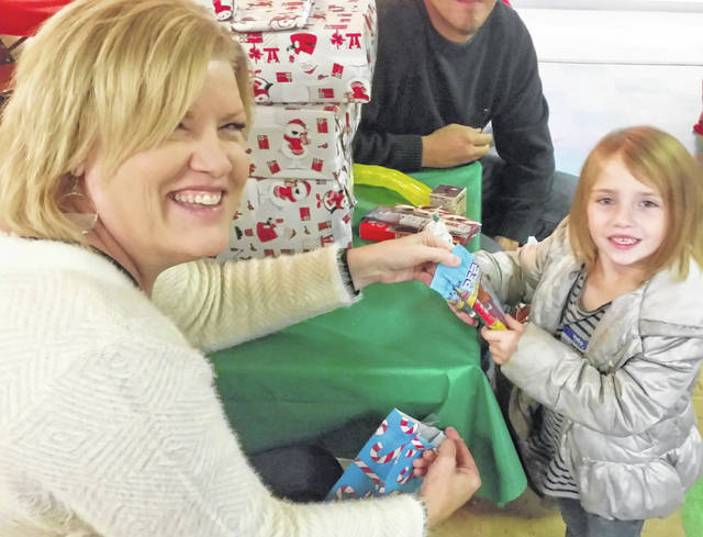 Kathy Kahle hands Starlenia Thompson a gift at the Spencerville VFW's annual Christmas Party for Underprivileged Children.