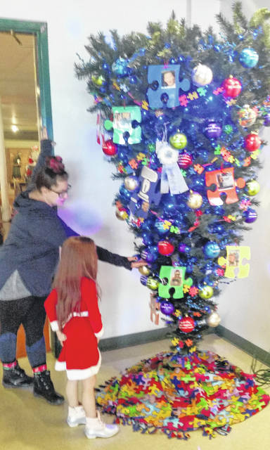 """Amber and Charlotte Hiebert check out the People's Choice Award winner, """"Zeroing in on Zane"""" at the Christmas Tree Festival."""