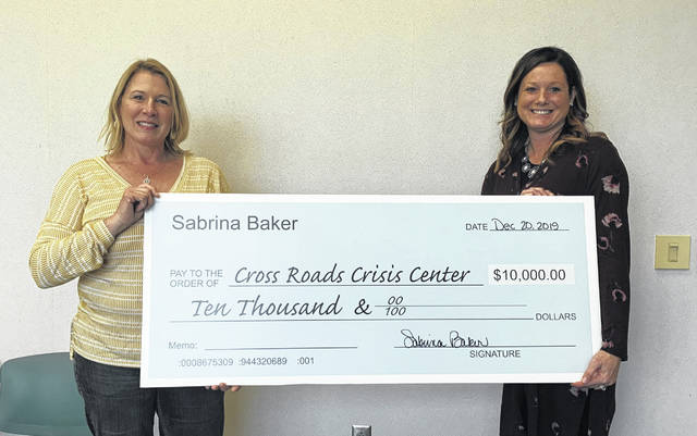 Sabrina Daley-Baker, left, and her husband, Phil, donated $10,000 to executive director Christel Keller, right, and the Crossroads Crisis Center in Lima.