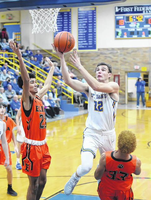 Jordan Brown of Delphos St. John's puts up a shot against Elida's Isaac Manley, left, and Devon Barnett during Saturday night's game Delphos.