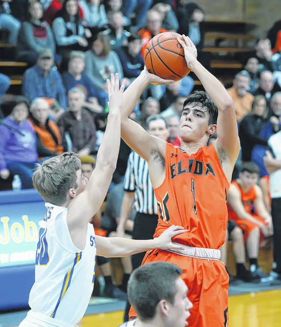 Elida's Dylan Buetner puts up a shot against Landon Elwer of Delphos St. John's during Saturday night's game in Delphos.