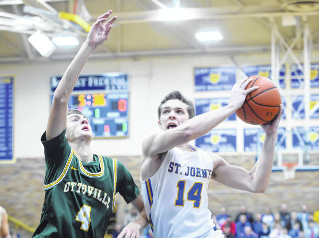 Aiden Rode of Delphos St. John's puts up a shot against Ottoville's Kyle Manns during Saturday night's game in Delphos.