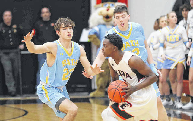 Bath's #23 Ian Armentrout, left, and Andrew Stahr double team Elida's Quan Moore during Friday night's game at the Elida Fieldhouse.
