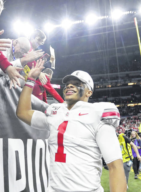 Ohio State quarterback Justin Fields (1) celebrates with fans following the team's Big Ten championship NCAA college football game against Wisconsin, early Sunday, Dec. 8, 2019, in Indianapolis. Ohio State won 34-21. (AP Photo/Michael Conroy)