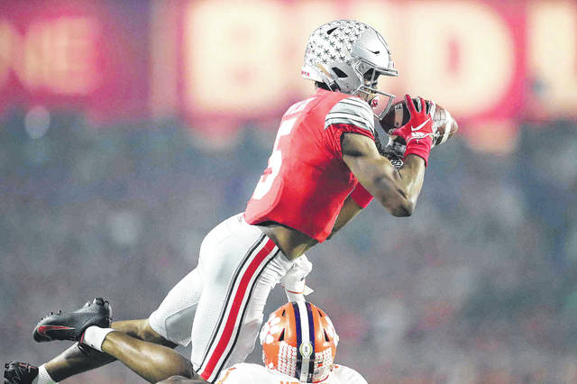 Ohio State wide reciever Garrett Wilson goes up high to make a first quarter reception over Clemson cornerback Derion Kendrick during the Playstation Fiesta Bowl semi - final game at State Farm stadium Saturday.