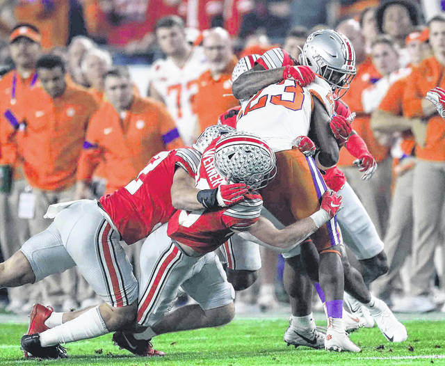 Ohio State linebacker Tuf Borland (left) and Ohio State linebacker Pete Werner and Ohio State defensive end Tyreke Smith (right) all combine to wrap up Clemson running back Lyn-J Dixon during the Playstation Fiesta Bowl semifinal game at State Farm stadium Saturday.